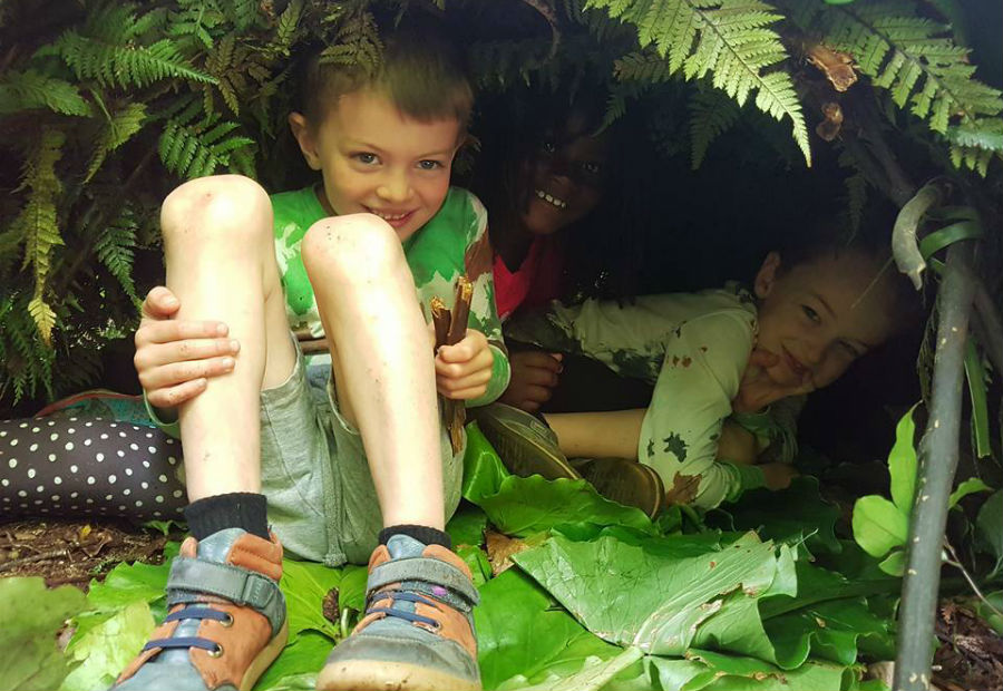 Children hiding out in their bush shelter creations at one of Pukeiti's family events